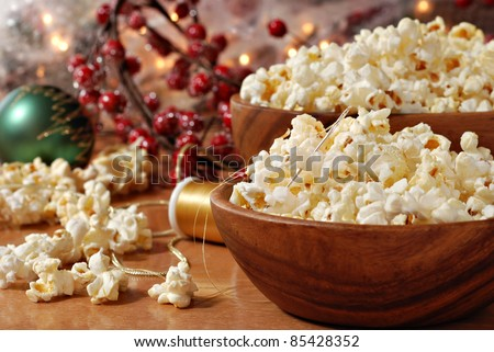Christmas still life of popcorn being strung together to create garland for the tree.  Decorations and berries in soft focus in background.  Closeup with shallow dof. - stock photo