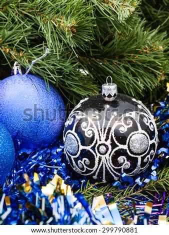 Christmas still life - one black glass close up and two blue and violet Christmas balls, tinsel on Xmas tree background - stock photo