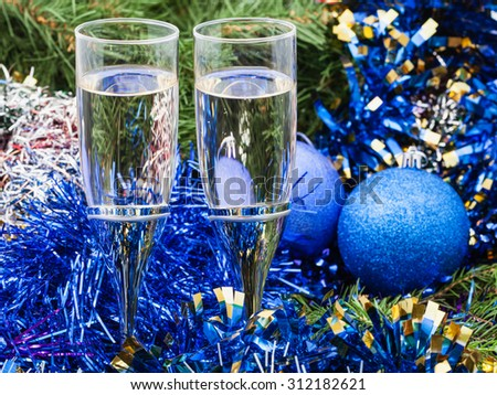Christmas still life - Two glasses of champagne with blue Xmas balls and tinsel and on Christmas tree background
