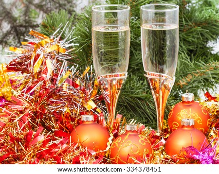 Christmas still life - Two glasses of champagne with golden Xmas decorations on Christmas tree background - stock photo