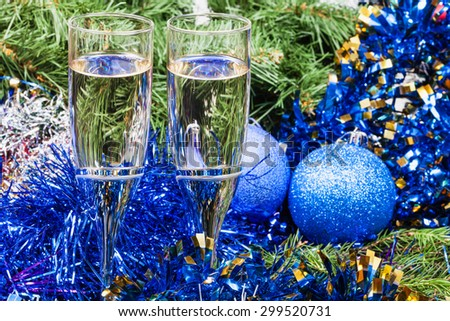 Christmas still life - Two glasses of sparkling wine with blue Xmas balls and tinsel on Christmas tree background - stock photo