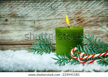 Christmas still life with a burning candle standing in winter snow with pine foliage and colorful red and white striped candy canes, wooden background with copyspace - stock photo