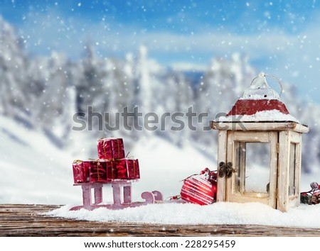 Christmas still life with lantern, gift and sledge. Blur landscape on background - stock photo