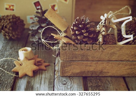 Christmas still life with pine cones, Christmas toys and ginger biscuits on wooden background. Retro style