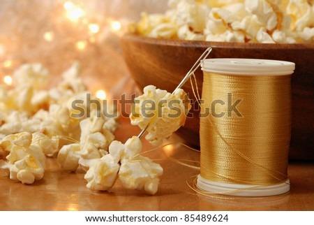 Christmas still life with popcorn being threaded onto shiny gold thread to create garland for the tree.  Macro with shallow dof.  Selective focus on needle. - stock photo