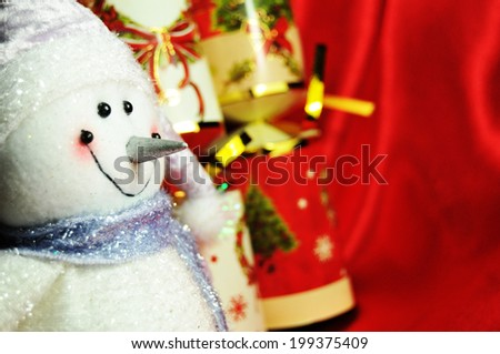 Christmas still-life with snowman against red silk background  - stock photo