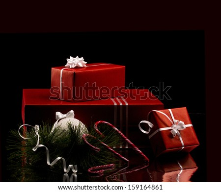 christmas still - several red boxes with white bow, candycane and branch of firtree on black dark background - stock photo