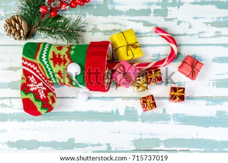 Christmas stocking and branch of spruce with cones lies on a white-blue wooden surface. From it stick out gifts and a stick. Top view. Horizontal shot.