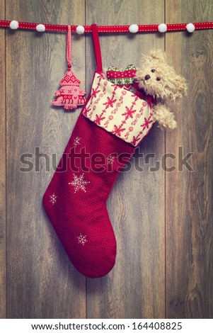 Christmas stocking filled with teddy bear with vintage feel - stock photo