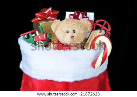 Christmas Stocking Filled With Toys, Candy Cane and Presents over black background - stock photo