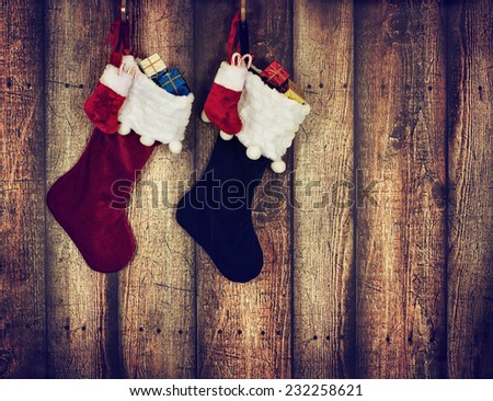 Christmas stocking hanging against rustic wood background. Vintage filter effects.  - stock photo