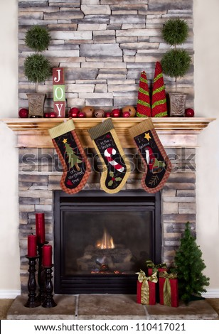 Christmas stocking hanging from a mantel or fireplace, decorated for Christmas with fire glowing. - stock photo