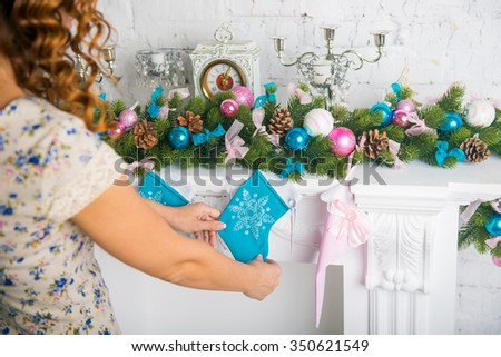 Christmas stocking on fireplace background. home decoration Christmas socks. woman's hands decorate the house for Christmas - stock photo