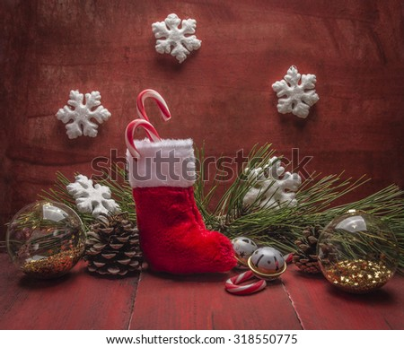 Christmas stocking Pine cones and branches snowflake and candy Christmas decorations  on red wooden rustic background  close up - stock photo