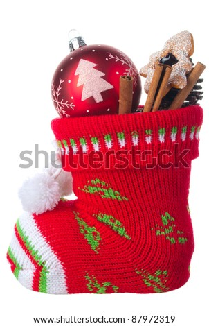 Christmas stocking stuffed with ball, cinnamon sticks and a cookie, isolated on a white background