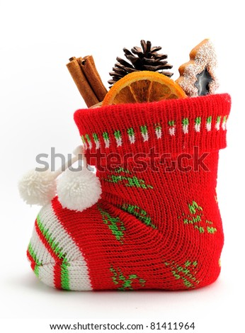 Christmas stocking stuffed with candy, fruit, cinnamon sticks and cone isolated on white background - stock photo