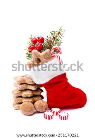 Christmas stocking, walnuts, candy and cookies on white background - stock photo