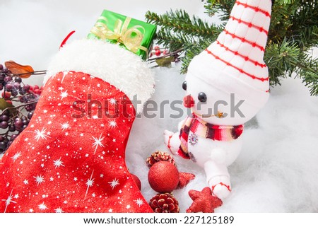 Christmas stocking with gift box , snowman and christmas decoration  on white snow background