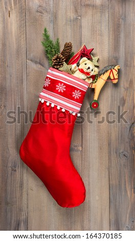 christmas stocking with nostalgic vintage toys decoration and pine branch over wooden background - stock photo