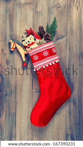 christmas stocking with nostalgic vintage toys decoration and pine branch over wooden background. retro style toned picture - stock photo