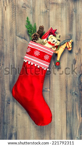 christmas stocking with nostalgic vintage toys decoration and pine branch over wooden background. vintage style toned picture - stock photo