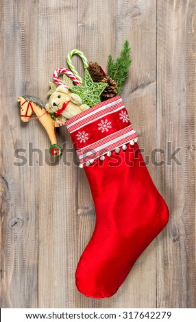 Christmas stocking with nostalgic vintage toys decoration and pine branch over wooden background.  - stock photo