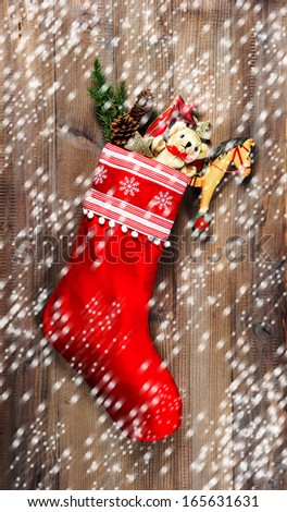 christmas stocking with old toys decoration and pine branch over wooden background. nostalgic vintage style picture with falling snow effect - stock photo