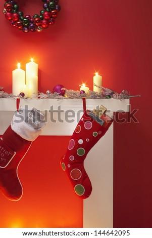 Christmas stockings hanging over fireplace - stock photo