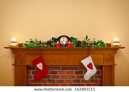Christmas stockings hanging over the fireplace at midnight on Christmas Eve, the mantlepiece is decorated with festive holly and ivy garland plus candles. Plenty of copy space to add your own message. - stock photo