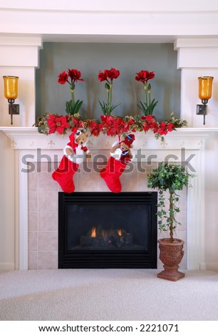 Christmas Stockings on the Mantle - Red and white fur christmas stockings hang on the mantle above the fireplace. - stock photo