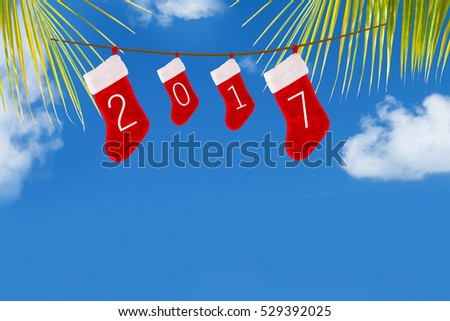 Christmas stockings with sign 2017 hanging on coconut palm tree leafs at beach with turquoise water