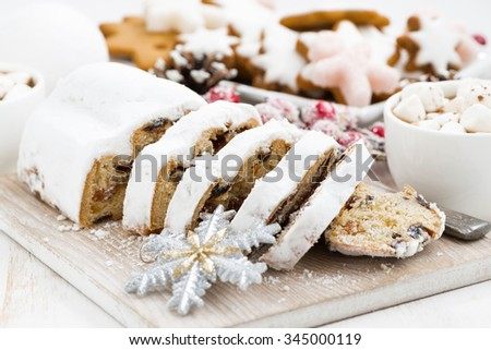 Christmas Stollen on a wooden board and sweets, closeup