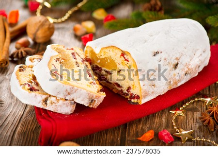 Christmas Stollen. Traditional Sweet Fruit Loaf with Icing Sugar. Xmas holiday table setting, decorated with garlands, baubles, wallnuts, hazelnuts, cinnamon sticks. - stock photo