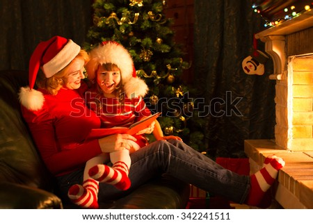 Christmas story time with mother and child daughter in front of fireplace at x-mas tree - stock photo