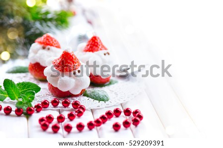 Christmas Strawberry Santa Dessert stuffed with whipped cream. Funny Winter New year Gourmet food. Cheesecake. Xmas party food idea, dinner table setting. Happy Winter Holiday served table