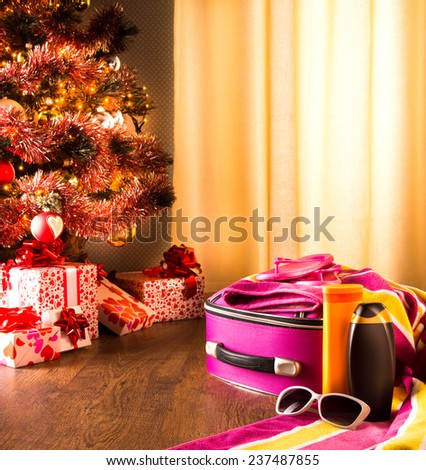 Christmas sun holidays with colorful luggage, sunglasses and beach accessories. - stock photo