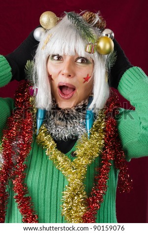 Christmas Surprise - festive decorated woman. Studio shot against a red background.