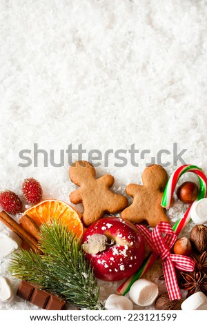 Christmas sweets on snow with copy space for text. - stock photo