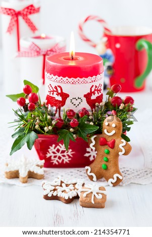 Christmas table decorated with candle,flowers and gingerbread - stock photo