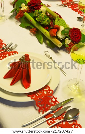 Christmas table decorated with red napkins and flower arrangement - stock photo
