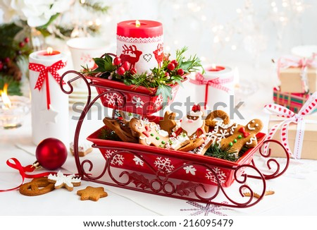 Christmas table decoration with biscuits,flowers and candles - stock photo