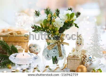 Christmas table decoration with flowers,gifts and baubles - stock photo
