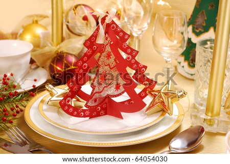 christmas table decoration with paper christmas tree shape on plate in red,golden and white colors - stock photo