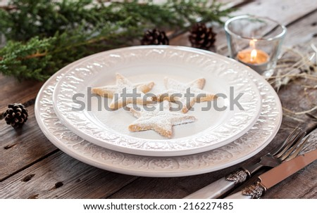 Christmas table - elegant white plate with cookies, natural pine tree branch and pinecones on vintage planked wood. Rural or rustic style table setting. - stock photo