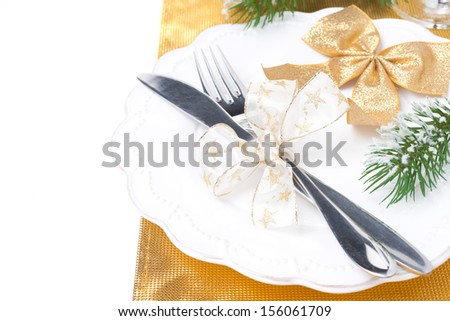 Christmas table place setting in golden tones, isolated on white background - stock photo