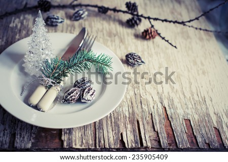 Christmas table place setting with christmas pine-cone and plate, knife and fork / Christmas holidays background - stock photo
