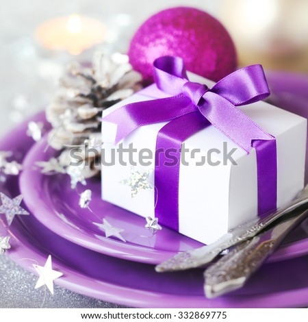 Christmas table setting - Christmas gift tied with purple ribbon on purple plates with festive decorations at the background - stock photo