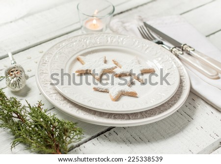 Christmas table setting - elegant white plate with cookies, natural pine tree branch and candle on vintage planked wood. Rustic or vintage style. - stock photo