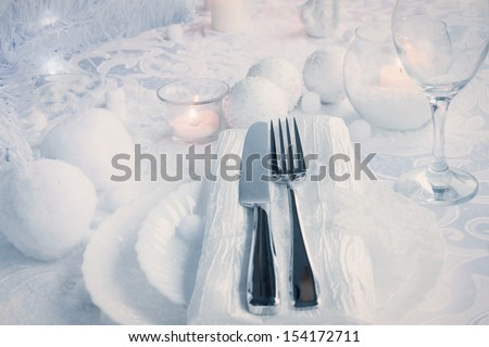 Christmas table setting. Fork and knife in elegant holiday setting with snow and white ornaments - stock photo