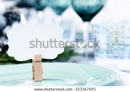 Christmas table setting in blue white and green theme with empty place card  - stock photo